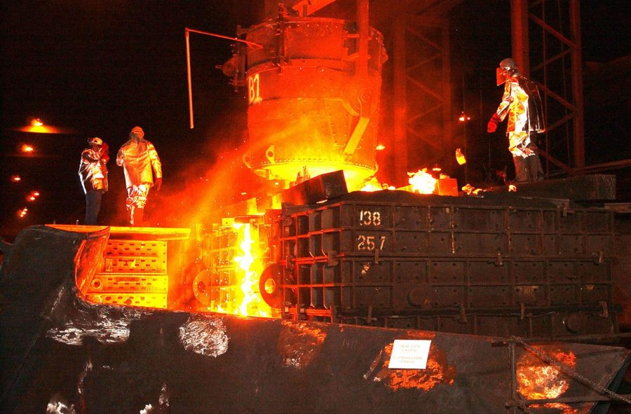 Foundry workers pour molten steel into mold in Amite, LA.