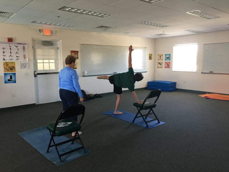 Ms. Bresnahan, the PC yoga teacher, instructing a student.