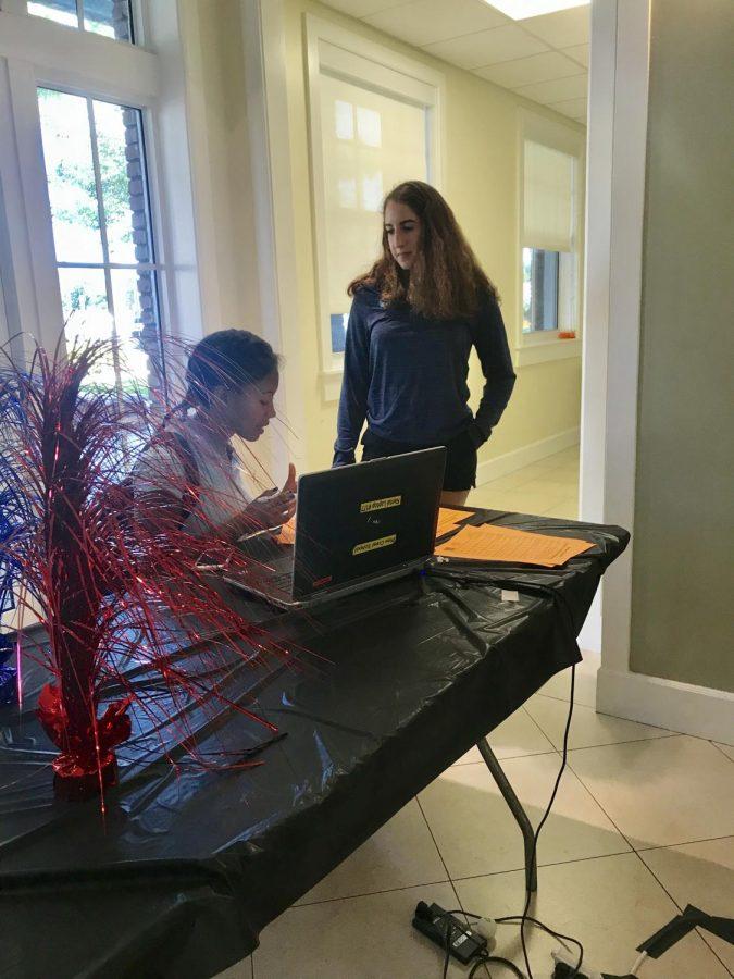 Alexa Jacques explains voting procedures to Bianca Simons during the Post-AP Political Science mock election.
