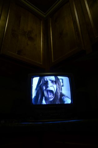 A horror film is presented on the television screen.